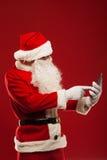 使用在红色的现代圣诞老人片剂个人计算机 库存照片