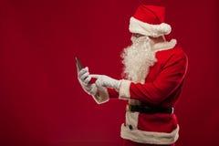 使用在红色背景的现代圣诞老人片剂个人计算机 Christma 图库摄影