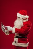 使用在红色背景的现代圣诞老人片剂个人计算机 Christma 免版税库存图片