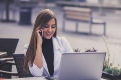 使用在线的可爱的妇女一台膝上型计算机和叫顾客ser 免版税库存照片