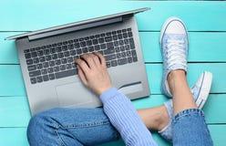 使用在绿松石木桌上的一台膝上型计算机 顶视图 现代青年时期 一代Z 在互联网上的网上工作 图库摄影