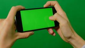 使用在绿色背景的女实业家一个空白的绿色屏幕手机 股票录像