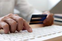 使用在网上支付的信用卡,为网络购物使用一个智能手机,一只男性手拿着信用卡 图库摄影