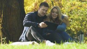 使用在网上片剂室外,无线互联网、购物或者售票的年轻夫妇 股票录像