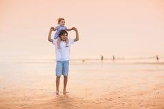使用在美丽的海滩的兄弟和小姐妹在日落 免版税库存图片