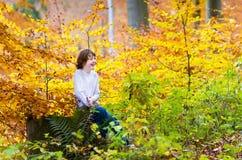 使用在美丽的秋天公园的愉快的男孩 免版税库存图片