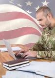 使用在美国国旗前面的战士一台膝上型计算机 库存图片