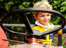 使用在老拖拉机的小男孩 免版税库存照片