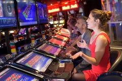 使用在老虎机的夫妇在赌博娱乐场 免版税图库摄影