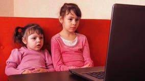 使用在膝上型计算机的孩子 两个小女孩在膝上型计算机打印 两个姐妹坐看膝部的橙色长沙发 股票录像