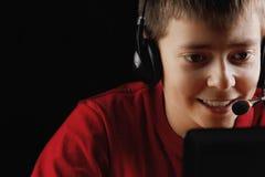 使用在膝上型计算机的微笑的少年 库存照片