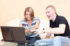 使用在膝上型计算机的比赛的二个年轻人。 免版税库存照片
