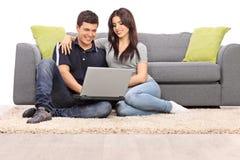 使用在膝上型计算机的年轻夫妇 免版税库存照片