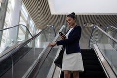 使用在自动扶梯的美丽的年轻mixed-race女实业家手机在现代办公室 图库摄影