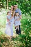 使用在自然和拥抱两个女儿的妈妈和爸爸 免版税库存图片