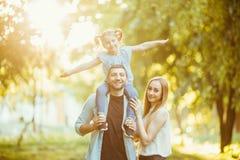 使用在自然在秋天的黄昏阳光,夏天下的愉快的家庭 使用在Th的草的母亲、父亲和女儿 免版税库存图片