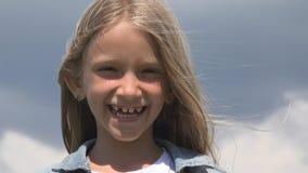 使用在自然笑的女孩亲吻,孩子面孔的儿童画象微笑在公园 图库摄影