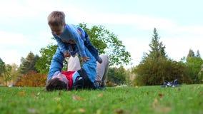 使用在草坪的愉快的家庭 一个年轻爱恋的父亲提高了在他的头,儿童微笑上的儿童上流 成块 股票视频