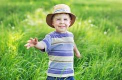 使用在草甸的一个逗人喜爱的小男孩的画象 免版税库存照片