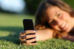 使用在草的一个巧妙的电话关闭一只愉快的青少年的女孩手 免版税库存照片