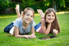 使用在草的两个愉快的女孩数字式片剂在公园 免版税图库摄影