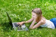 使用在草的女孩膝上型计算机 库存照片