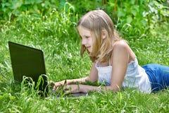 使用在草的女孩膝上型计算机 图库摄影