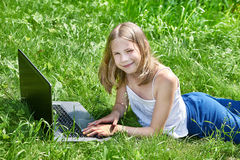 使用在草的女孩膝上型计算机 免版税图库摄影