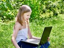 使用在草的女孩膝上型计算机 免版税库存照片