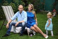 使用在草的愉快的年轻家庭 爸爸、妈妈和小美丽的女儿 一对年轻夫妇坐deckchairs 库存照片