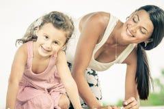 使用在草的母亲和女儿在天时间 库存图片