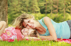 年轻使用在草的母亲和她的小女儿 免版税库存照片