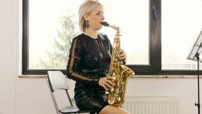 使用在萨克斯管的美丽的萨克斯管吹奏者妇女在客厅 股票视频