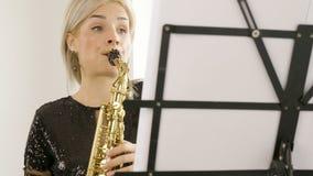 使用在萨克斯管的美丽的萨克斯管吹奏者妇女在客厅 影视素材