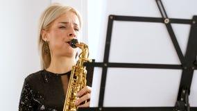 使用在萨克斯管的美丽的萨克斯管吹奏者妇女在客厅 股票录像
