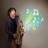 使用在萨克斯管的年轻音乐家,当音符explodin时 图库摄影