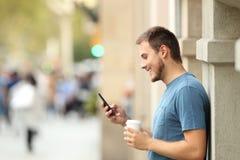 使用在街道上的一个人的侧视图一个巧妙的电话 免版税库存图片