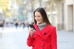 使用在街道上的夫人一个巧妙的电话在冬天 免版税图库摄影