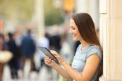 使用在街道上的女孩的侧视图一种片剂 免版税库存图片