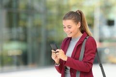 使用在街道上的年轻女实业家电话 图库摄影