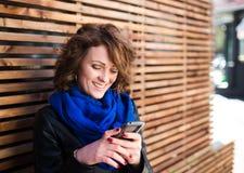 使用在街道上的微笑的少妇智能手机 图库摄影