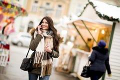使用在街道上的愉快的时尚妇女一个巧妙的电话在冬天 免版税库存照片