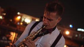 使用在街道上的观众前面的萨克斯管吹奏者在晚上 在他后是一个大大厦和水库的光 股票录像