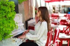 使用在街道咖啡馆的一架老钢琴的女孩 免版税库存照片