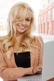 使用在街道的白肤金发的女实业家膝上型计算机 库存照片