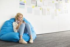 使用在装豆子小布袋椅子的微笑的女实业家手机在创造性的办公室 免版税库存照片