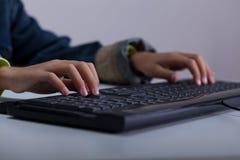 使用在计算机上的男孩特写镜头 图库摄影