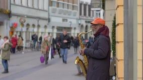 使用在路人人的萨克斯管的街道音乐乐器演奏者黑色老人在未聚焦的城市在慢动作 影视素材