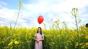 使用在路的愉快的小女孩在天时间 站立在领域和举行在手手提箱和气球上的她 股票录像