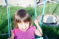 使用在跷跷板的小女孩室外在夏天 免版税图库摄影